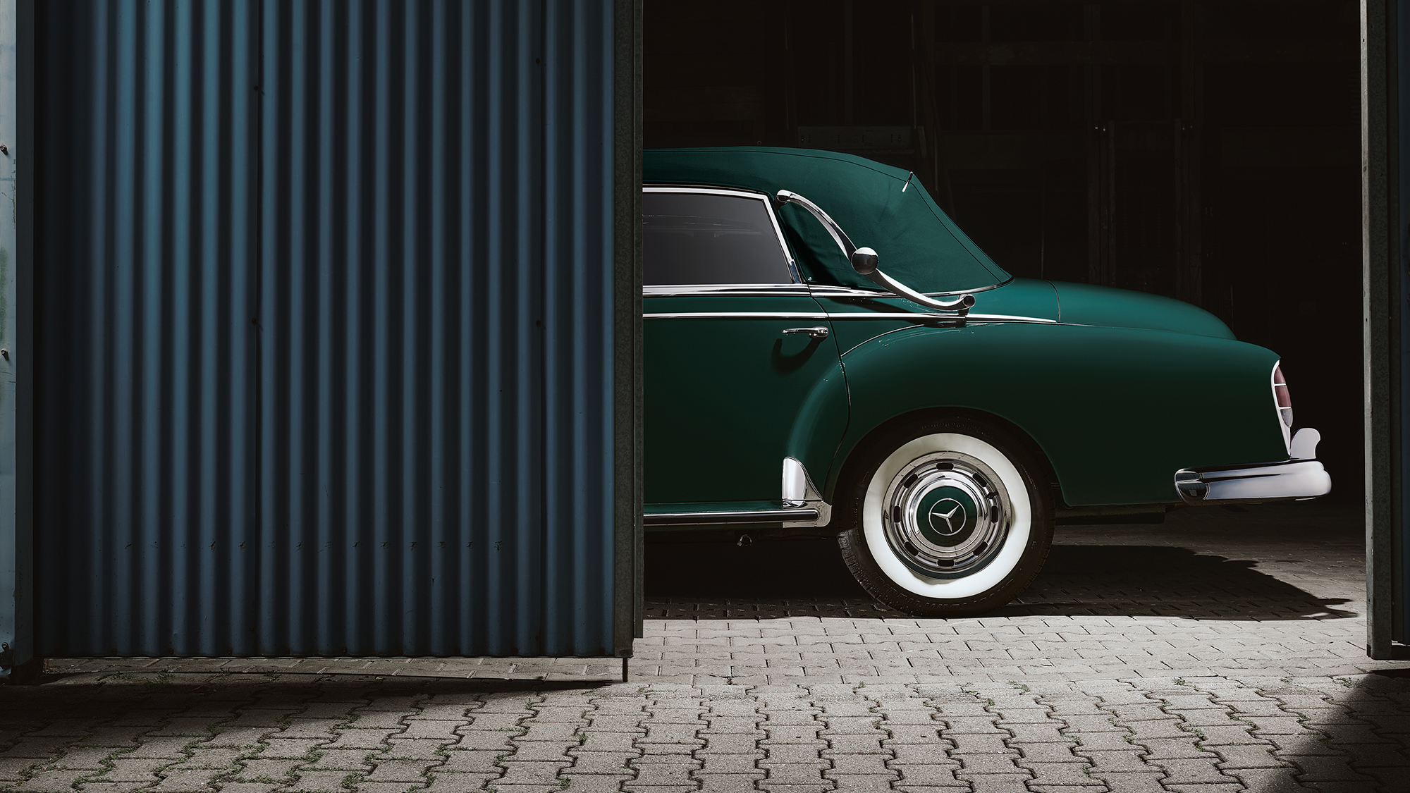 Elaborately staged automobile photo of a green Mercedes-Benz 300D classic car